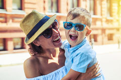 Small boy in sunglasses laughing in his mother's arms during wal Royalty Free Stock Photos