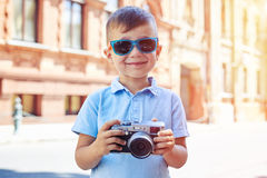 Small boy in sunglasses posing with camera on the background of Stock Images