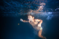 Small boy swimming underwater in pool at night Stock Photo