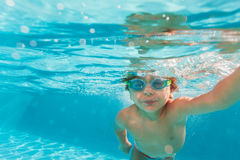 Small boy swimming wearing goggles under water. Small boy swimming wearing goggles under the crystal-clear water of swimming pool - underwater shoot Stock Photos