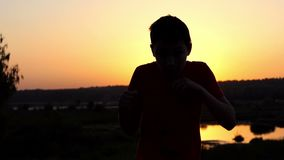 Small Boy Trains Boxing Hooks on a Lake Bank at Sunset in Autumn in Slo-Mo. A Gorgeous Close-Up of a Small Boy Who Trains Straight Blows, Uppercuts, Hooks, With stock video footage