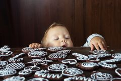 Small boy tries to grab traditional homemade Christmas ginger an. D chocolate cookie decorated with white sugar painting Stock Photo