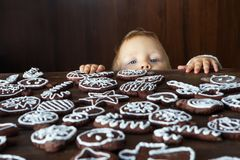 Small boy tries to grab traditional homemade Christmas ginger an. D chocolate cookie decorated with white sugar painting Royalty Free Stock Photography