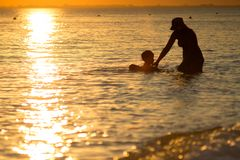Small boy trying to swim in sea with mother Stock Photo