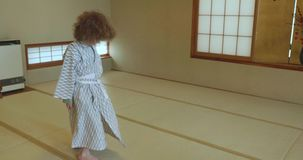 Small boy twists, twirls and dances while wearing traditional yukata. Small caucasian boy with long curly hair twists, twirls, dances and jumps on a Japanese stock video