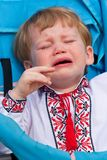 Small boy in ukrainian shirt crying in carriage Stock Photos