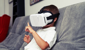 Small boy using VR-headset at home. Small boy is using VR-headset at home watching something in virtual reality Stock Photography