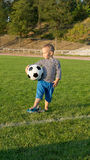 Small boy waiting with his soccer ball Stock Images