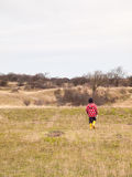 Small boy walking alone in a dunes in winter Royalty Free Stock Image