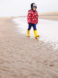 Small boy walking on the beach in winter Stock Image