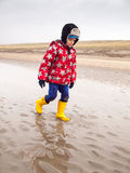 Small boy walking on the beach in winter Stock Photo