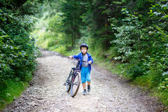 Small boy walking with bicycle on mountain trail Stock Image