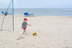 Small boy wants to fight off a soccer ball playing football on the beach sand. Royalty Free Stock Photography