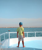 Small boy watches horizon on sailboat Stock Photography