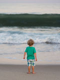 Small boy watching big wave approach Royalty Free Stock Images