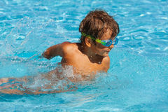 Small boy with water sport goggles swims in pool Stock Images