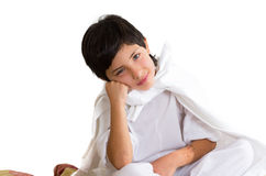 Small boy wearing all white sitting on quilt Royalty Free Stock Photography