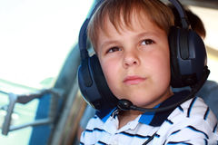 Small boy wearing headset in airplane Royalty Free Stock Photo