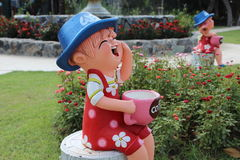 Small boy wearing red cloth holds the coffee cups , laughing doll. Small doll boy in the garden in front of resort Stock Photo