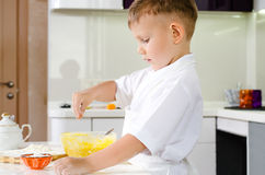 Small boy in a white apron standing baking Stock Photos