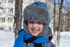 A small a boy winter sunlight a day to looks at us and smiles. stock photography