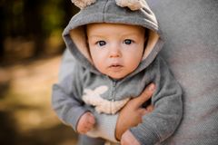 Free Small Boy With Pensive Gray Eyes Looks Attentively Sitting At The Fathers Hands Stock Photos - 111119543