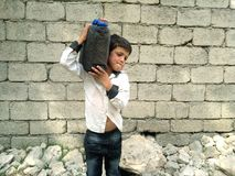 A small boy. Working hard, he is carrying a pot of water on his shoulder royalty free stock photo