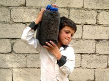 A small boy. Working hard, he is carrying a pot of water on his shoulder stock photos