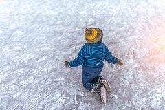 Small boy of 2-3 years old, wearing skirt, fell on ice his skates. Concept first lesson of skating support , failure and royalty free stock photography