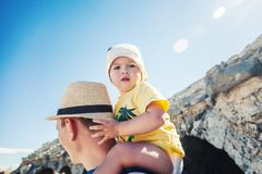 A small boy of 1-2 years sits on the shoulders of a young father. Traveling with a child royalty free stock image