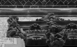 Small boys standing on the window. Shot in black and white, detail on the sculpture on the facade of this historic building representing some characters / Royalty Free Stock Photos