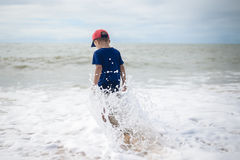 Small brave boy going to swim in rolling sea alone Royalty Free Stock Images