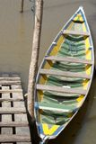 Small brazilian canoe. A small canoe yellow-and-green coloured, anchored to a woodmade harbor on the bank of an amazonian river. The colors evoke a hidden Stock Photos