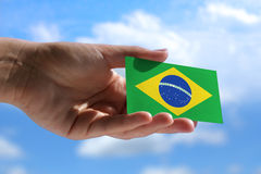 Small Brazilian flag. Against sky with cumulus clouds Stock Image