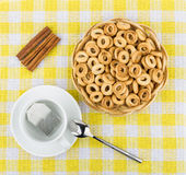 Small bread rings in basket, tea and sticks of cinnamon Royalty Free Stock Images