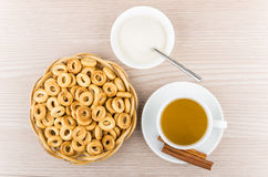 Small bread rings in wicker basket, tea, sticks of cinnamon Stock Image