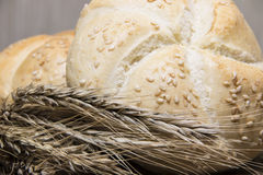 Small bread and wheat ear. On wooden desk Royalty Free Stock Photography