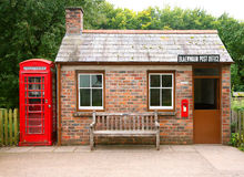 Small brick building. Small brick detached building of post office with a telephone box along side and wooden seat to the front. Two windows a door and a slate Stock Image