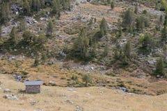 Small brick house on Rocky mountain slope with rare trees. Andor Stock Photos