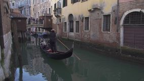 Small bridge at a canal in Venice with gondola, people and historic buildings stock video footage