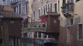Small bridge at a canal in Venice with people and historic buildings stock video