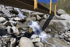 Small bridge crossing a mountain stream Royalty Free Stock Photography