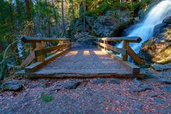 A small bridge in front of a waterfall stock images