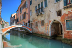 Small bridge over canal and old houses in Venice. Royalty Free Stock Photo