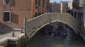 Small bridge at a canal in Venice with boat passing stock video