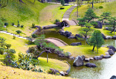 Small bridges over stream in a rocky, pine trees garden Stock Photography
