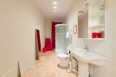 A small bright bathroom with a shower cabin. Sink and toilet bowl stock images