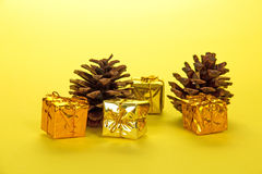 Small bright gift boxes and pine cones Stock Photography