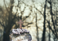 Small bronze cross. Small cross made of bronze and trees in background Royalty Free Stock Images