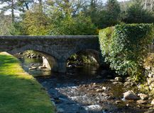 The small brook and arched stone bridge at the ancient Glendalough monastic site in the Wicklow mountains in Ireland Stock Photography